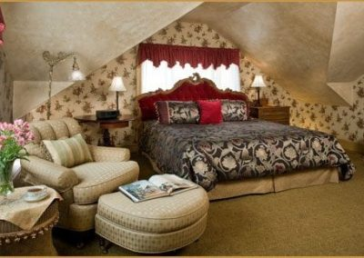 Photo of the Crown Jewel bedroom featuring a king bed with a dramatic red velvet headboard and cozy chair with ottoman