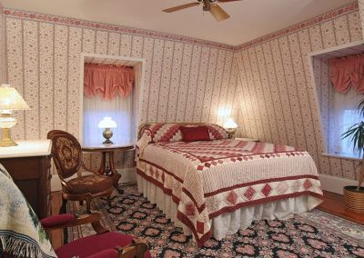 Buckingham guestroom Queen Bed with burgundy patterned quilt with black and rose floral area rug.