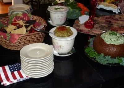 Prince Albert Hall dining room table set with American flag napkins for a Memorial Day celebration. Spinach dip in a rye bread bowl, guacamole spread and a basket of tortilla chips. are also on the table.