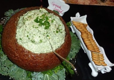 Close-up photo of a rye bread bowl with spinach spread in it. A white tray is next to it filled with crackers.