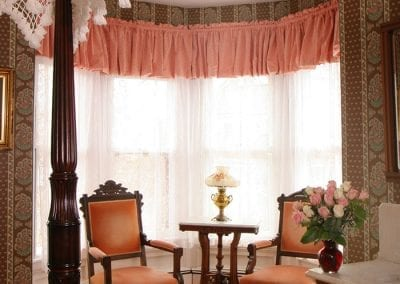 Prince of Wales bay window sitting area with two upholstered Victorian chairs