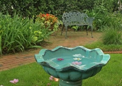 Closeup photo of a blue porcelain birdbath with purple and white daises floating in it. Lush gardens and iron settee in the background.