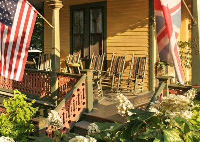 A close-up photo of the Prince Albert Hall porch on a very sunny day with rockers lining the porch and the American and British flags flying. White oakleaf hydrangea in the foreground.