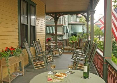 A close-up photo of the Prince Albert Hall porch with rockers lining the porch and the American and British flags flying. The flower box and planter are filled with red flowers and the table is set with white wine and crackers for two.