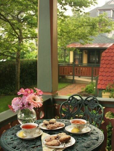 Close-up photo of a green bistro table on the corner of the Prince Albert Hall porch. Table has two china cups and saucers with two china plates with scones. A vase of colorful flowers is in the vase. The Regent's Park suite cottage is in the background.