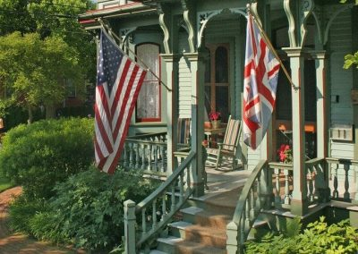 Close-up photo of The Queen Victoria front porch with the American and British flags flying.