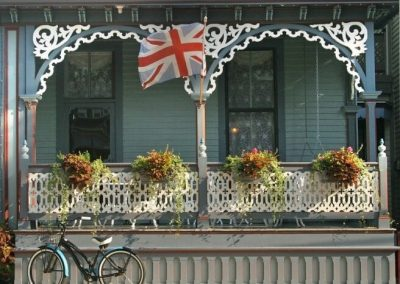 Photo of the Lord Melbourne porch taken from the street. There is a Queen Victoria bicycle parked in front of the porch. The flower boxes are overflowing with greenery and the British flag is swaying in the wind.