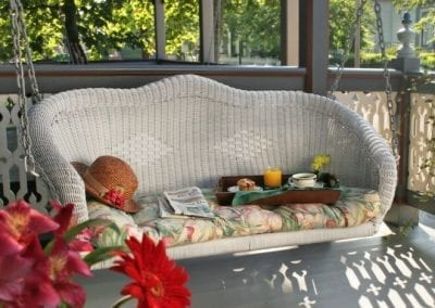 Close-up photo of the Lord Melbourne private porch wicker swing