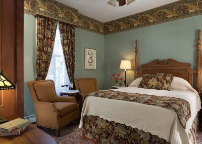 Photo of the Balmoral bedroom with the rich brown, rust, teal and gold floral bedding and draperies.