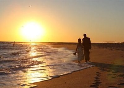 Guest Photos- Couple holding hands and walking next to the beach.