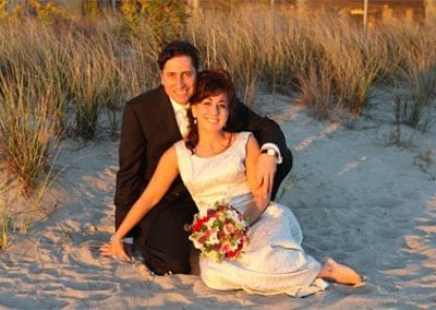 Guest Photos- Wedding picture. Man and woman sitting on sand with flowers