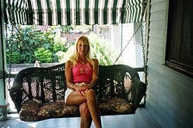 Guest Photos- woman sitting on porch swing at Queen Victoria Bed and Breakfast