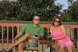 Guest Photos- Smiling couple on porch drinking wine at Queen Victoria.
