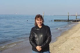 Guest Photos- Woman in black jacket standing next to the ocean.